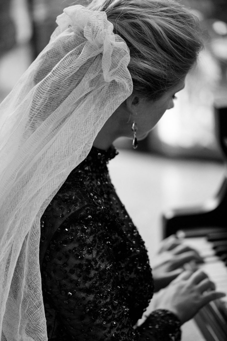Fine Art Black Tie Wedding Inspiration Shoot bride on piano with gathered veil