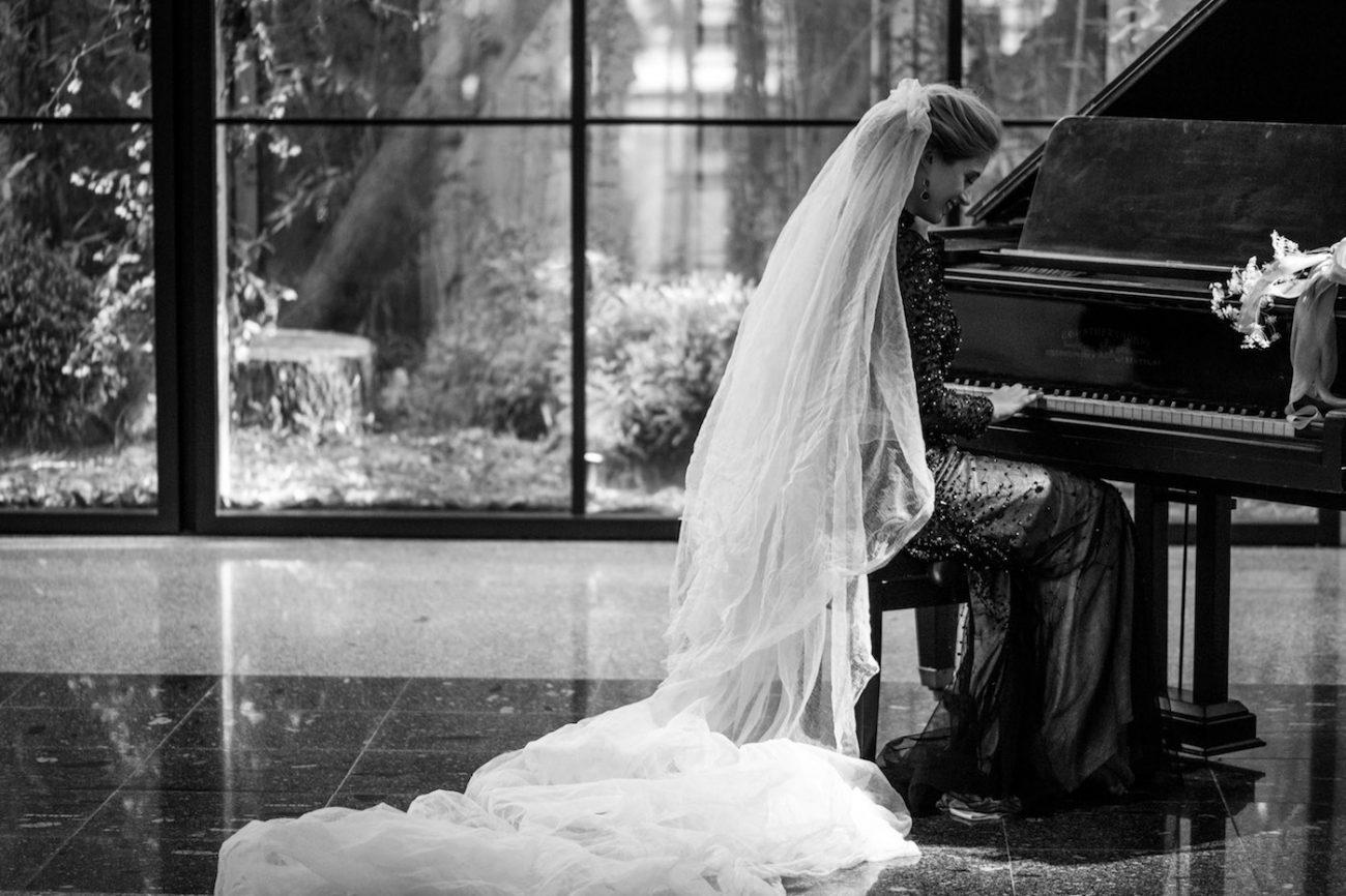 Fine Art Black Tie Wedding Inspiration Shoot bride on piano with veil