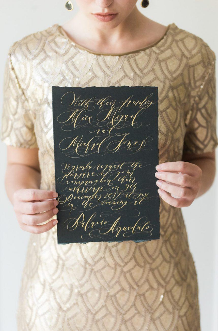 Fine Art Black Tie Wedding Inspiration Shoot bride with gold dress and black invitation