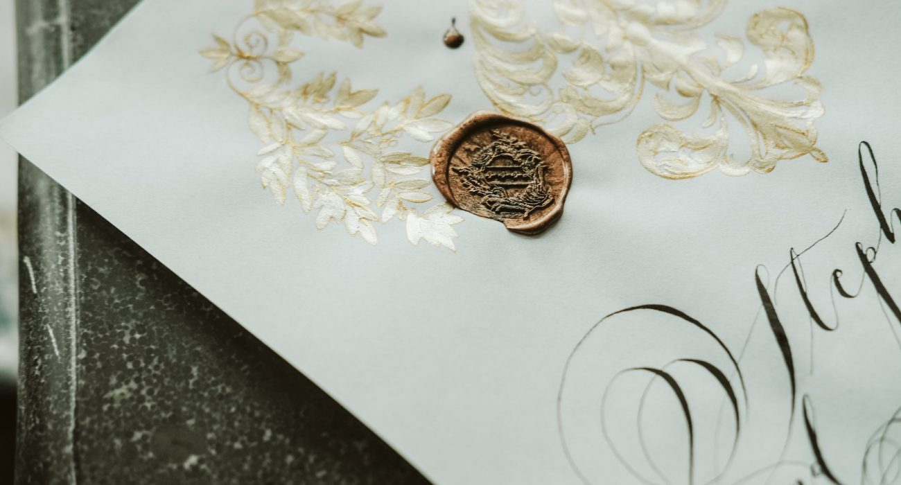 Invitation Glossary black calligraphy flourishes with gold painting and wax seal