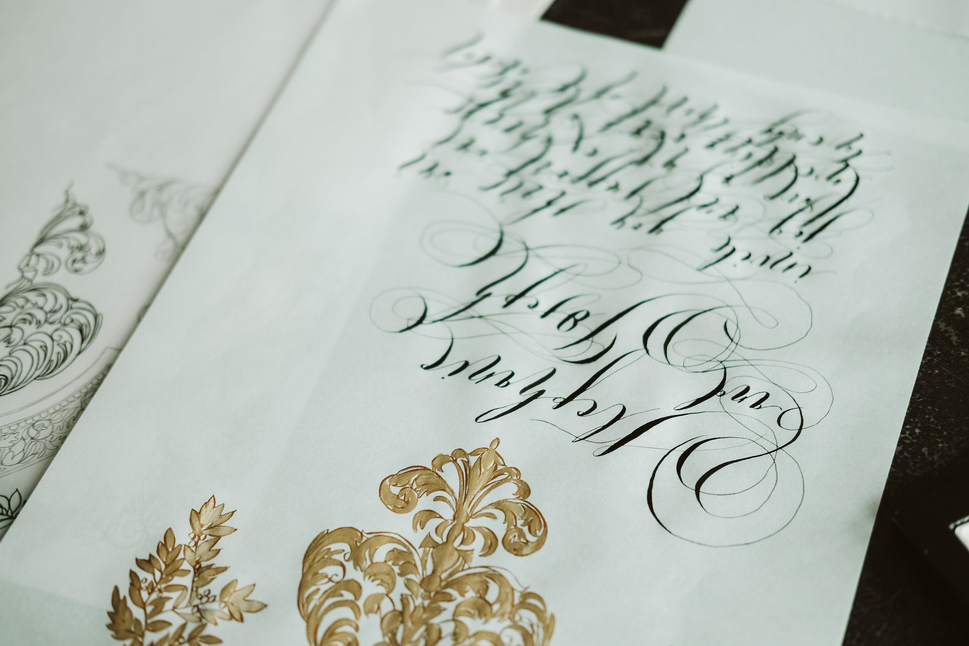 Invitation Glossary black calligraphy with gold design for weddings