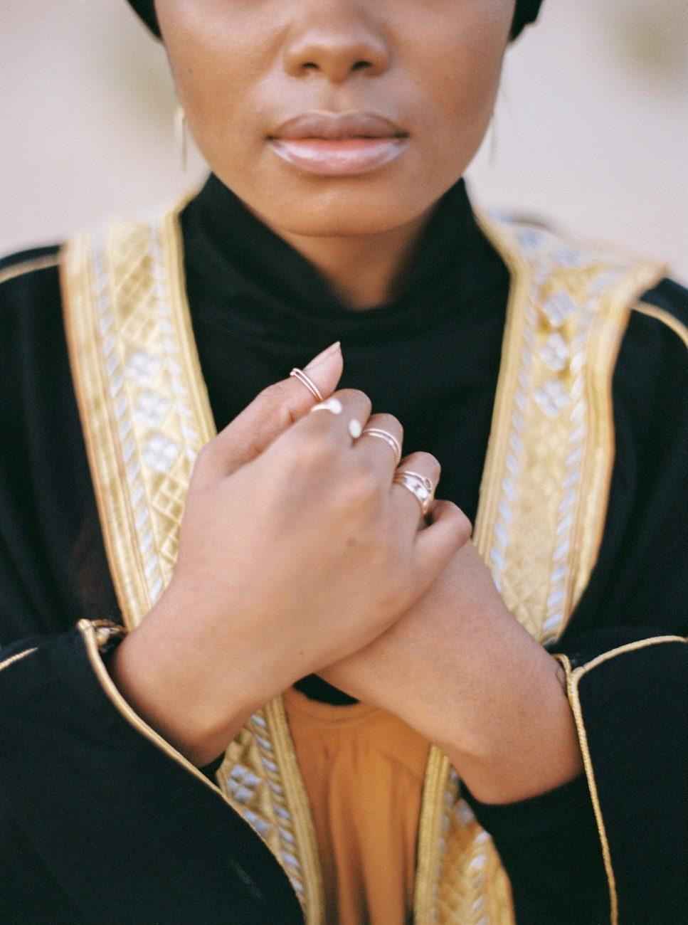 Desert fine art wedding inspiration bride with black robe with gold border