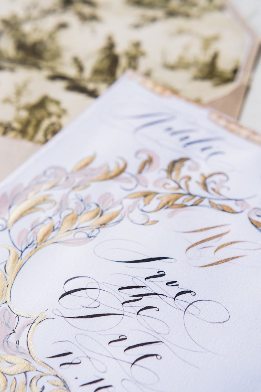 Tarnished gold hand painted details on a save the date card with pale blush accents and black calligraphy