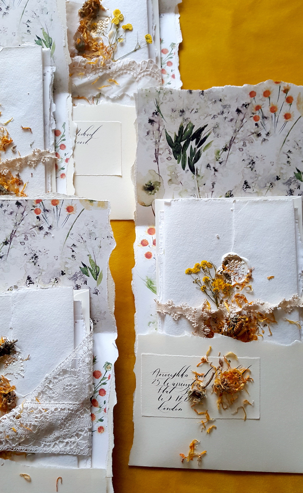 Bespoke Watercolour Wedding Invitations with the envelope open showing the lace ribbon and loose flowers inside