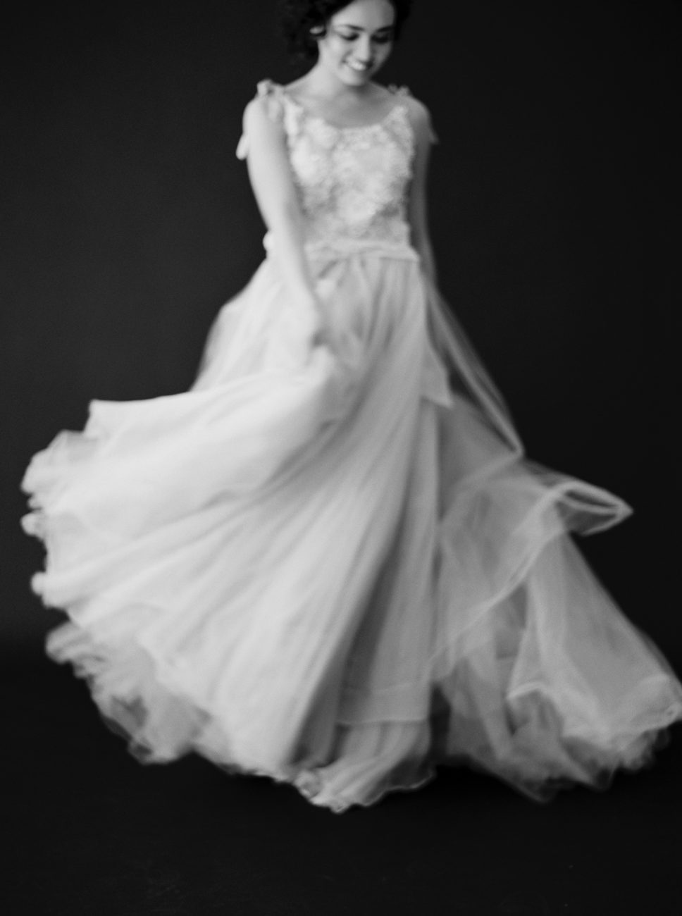 Moody Black Wedding Inspiration with bride moving her dress