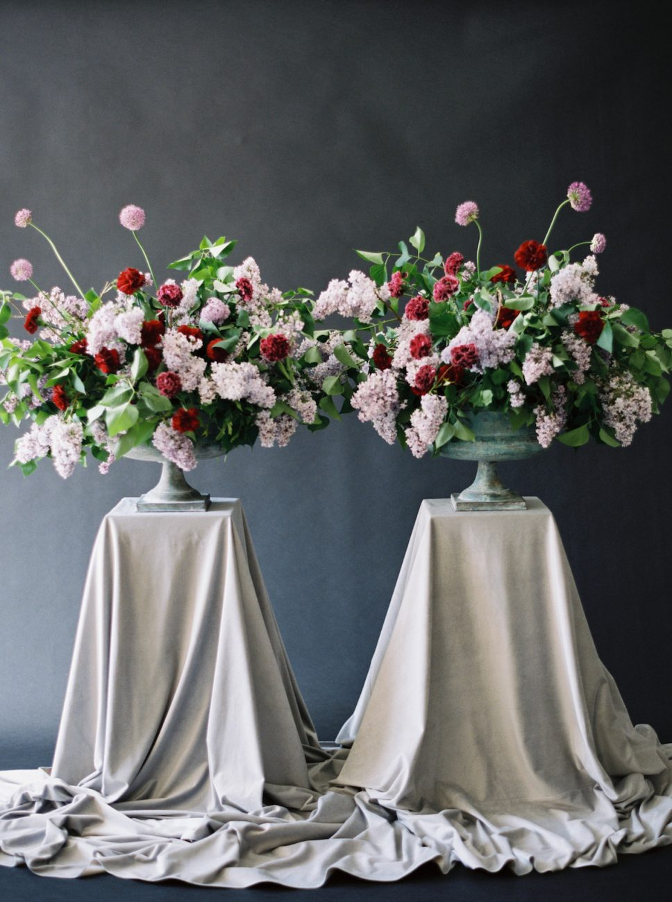 Moody Black Wedding Inspiration_two large flower urns with red and light pink flowers