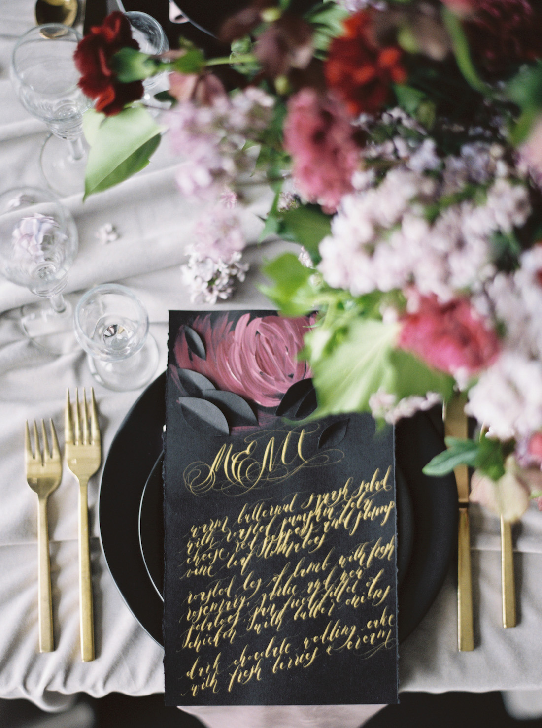 London Wedding Invitations with black wedding menu with gold calligraphy and dark pink flower cover with flowers from the table scape