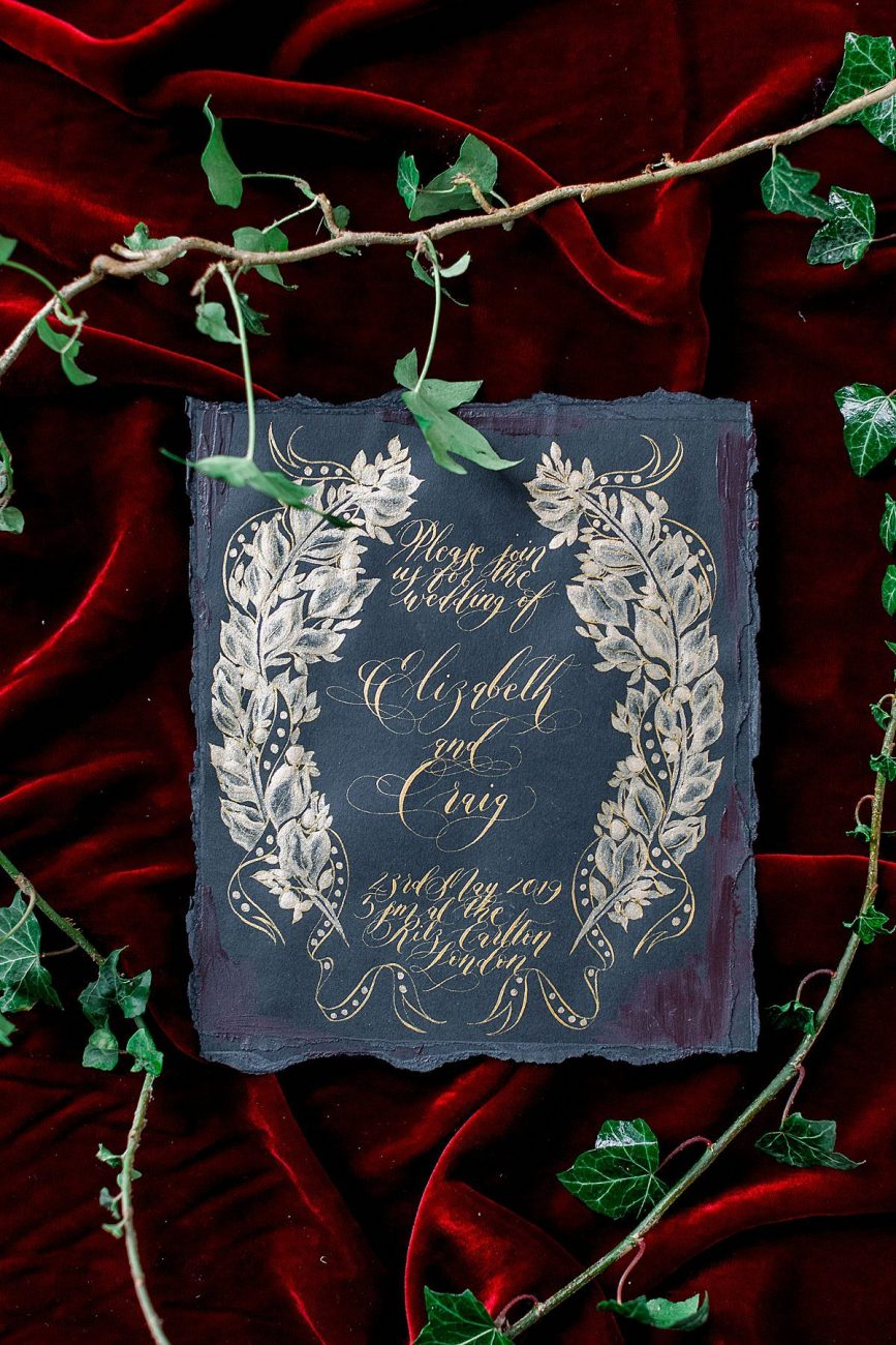 Baroque Wedding black invitation with a symmetrical gold wreath