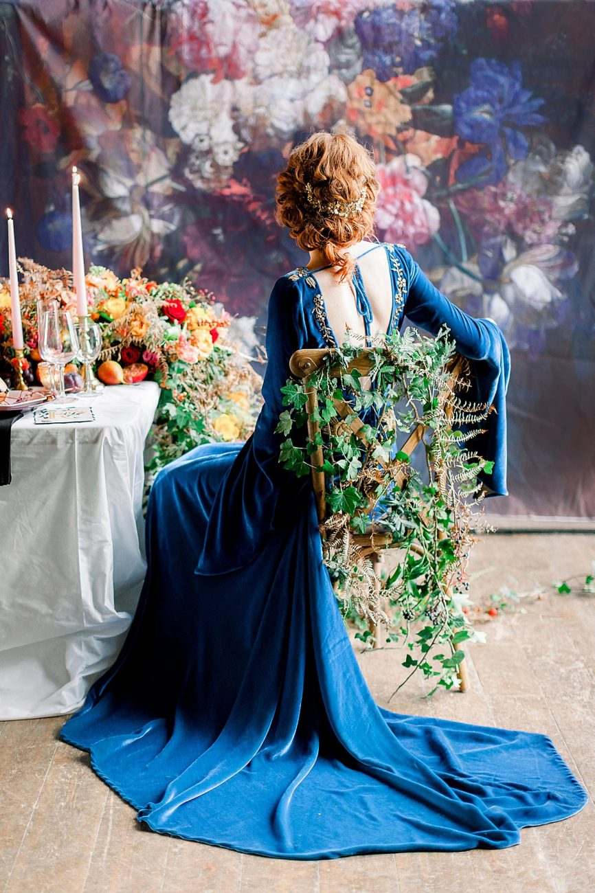 Baroque Wedding bride with blue velvet dress sitting on a chair with ivy