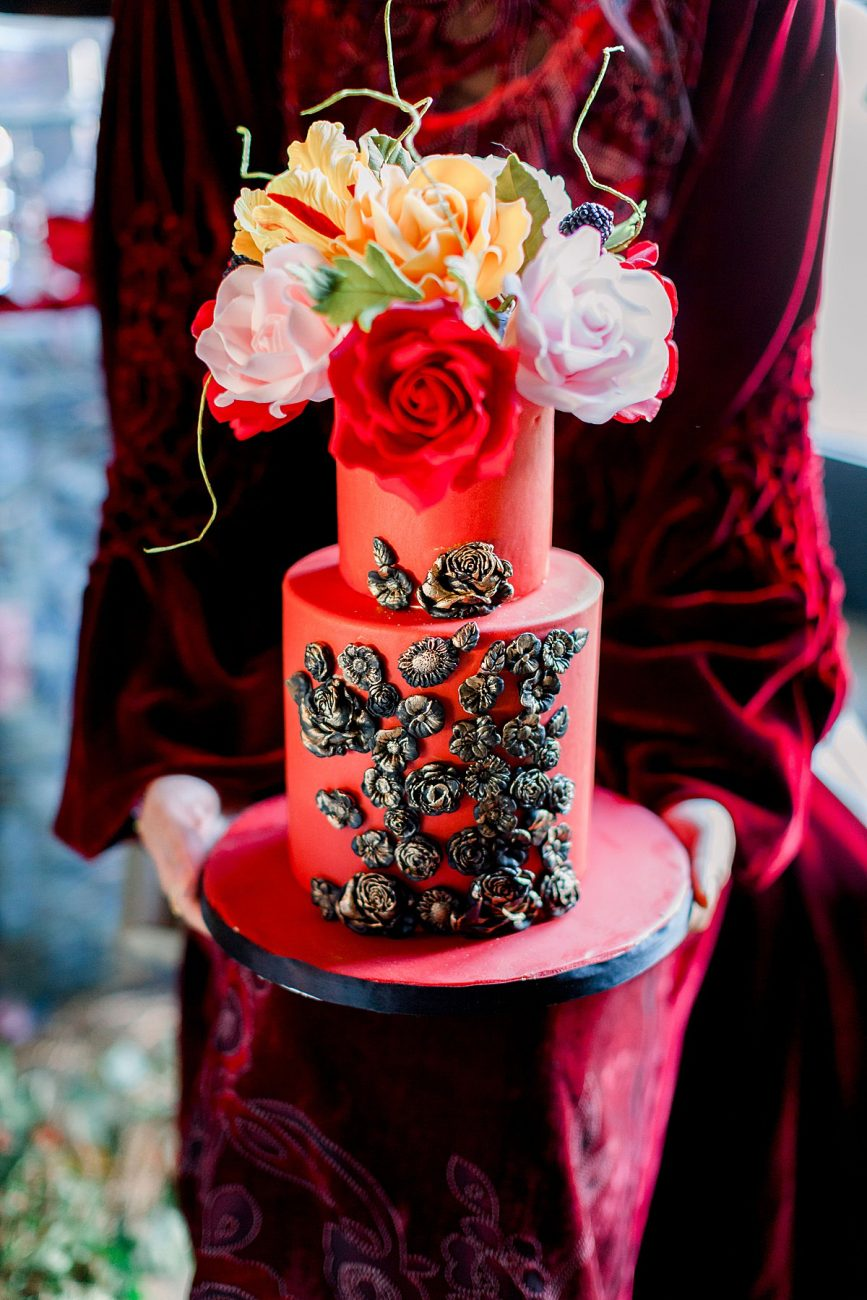 Baroque Wedding cake held by bride in a red velvet wedding dress