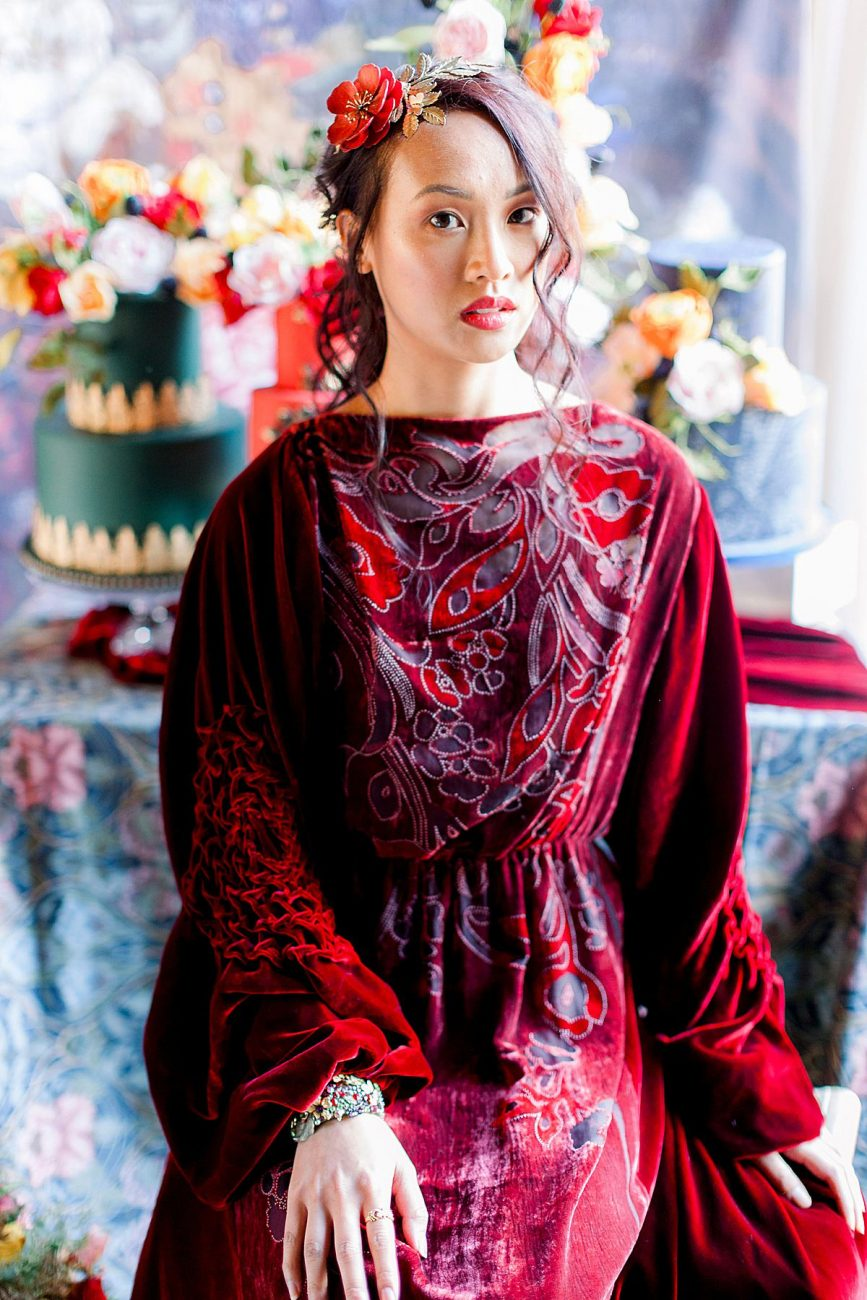 Baroque wedding inspiration with a bride in a red velvet dress sitting in front of cakes