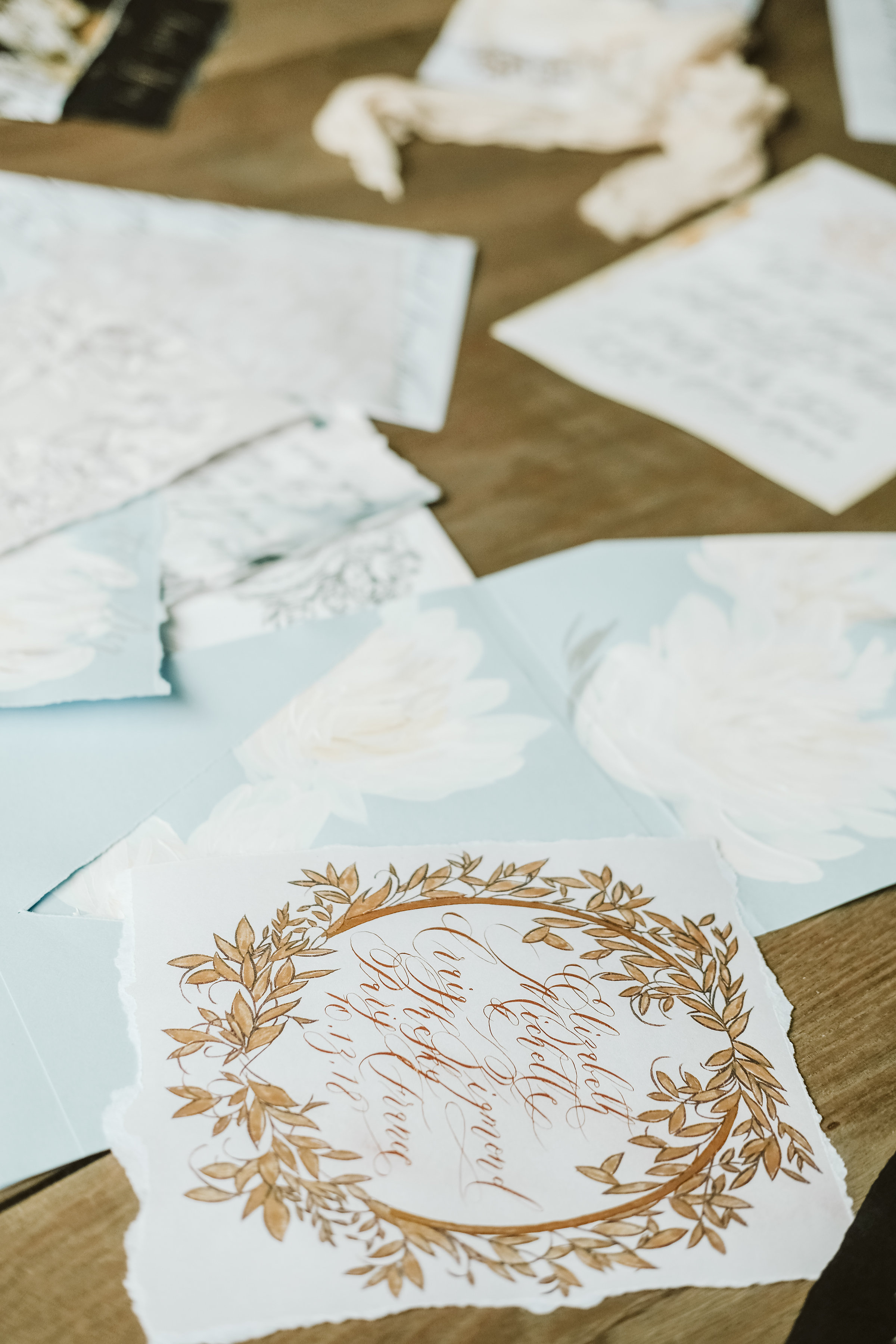 Illustrated wedding invitations with gold leaves design and gold calligraphy