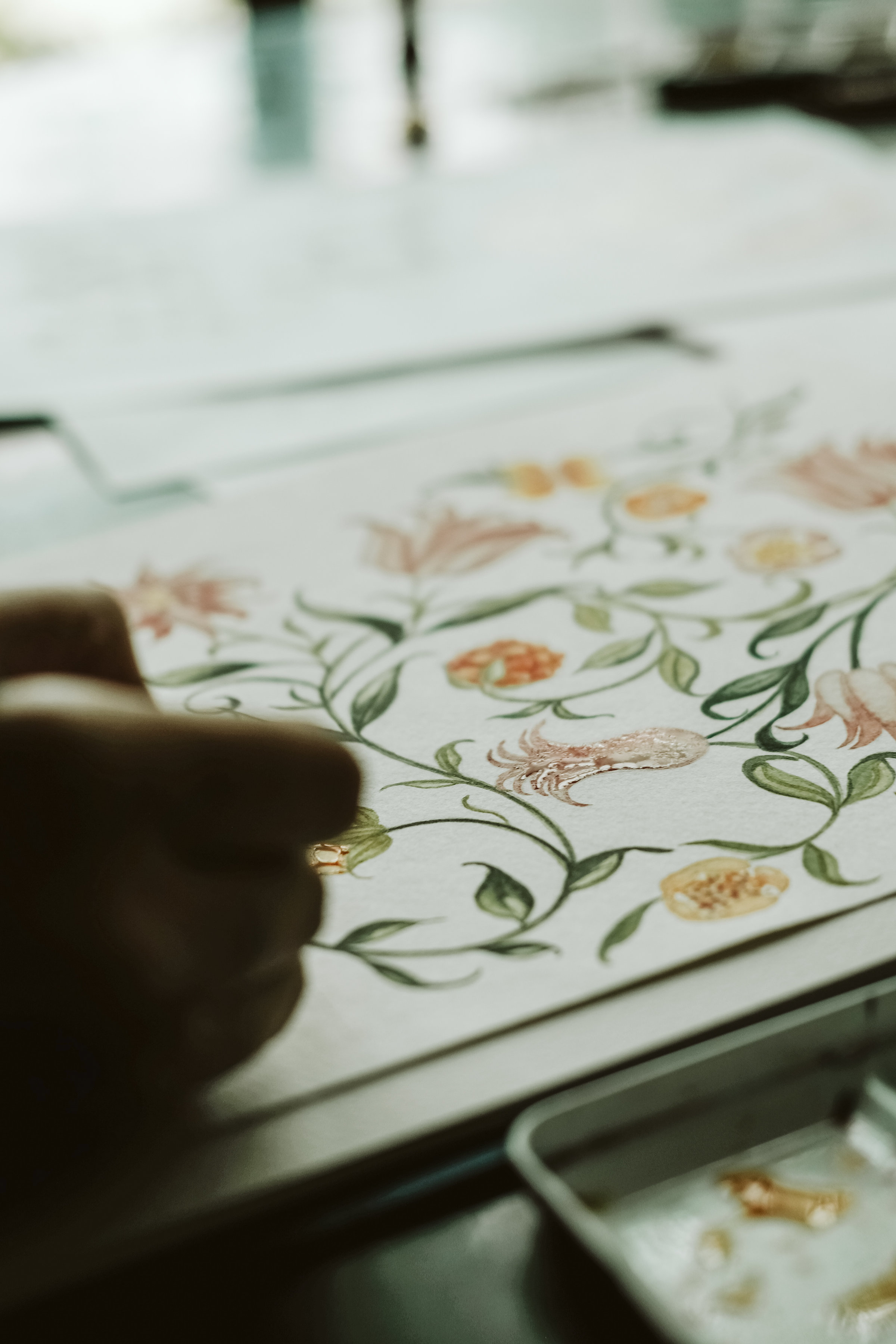 Illustrated wedding invitations with a watercolour palette on a desk