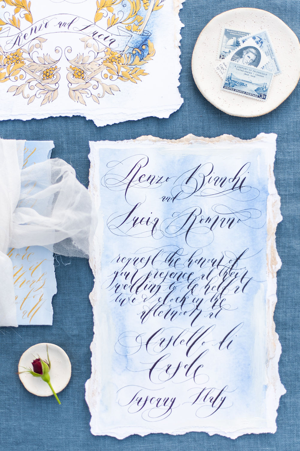 vow renewal invitation card with black calligraphy on a blue card