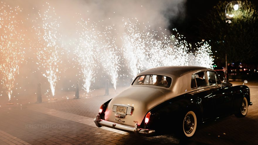Photograph of a black car leaving a wedding with huge sparklers