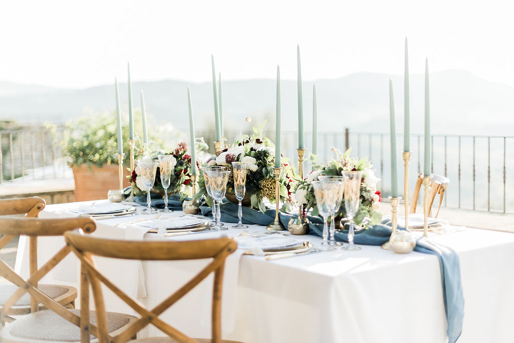 Table setting with gold patterned glasses, pale green candles and blue accents