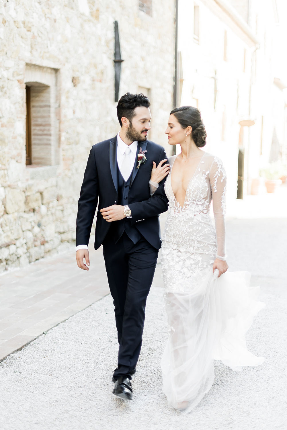 Destination weddings stationery tips with couple walking through village in Italy