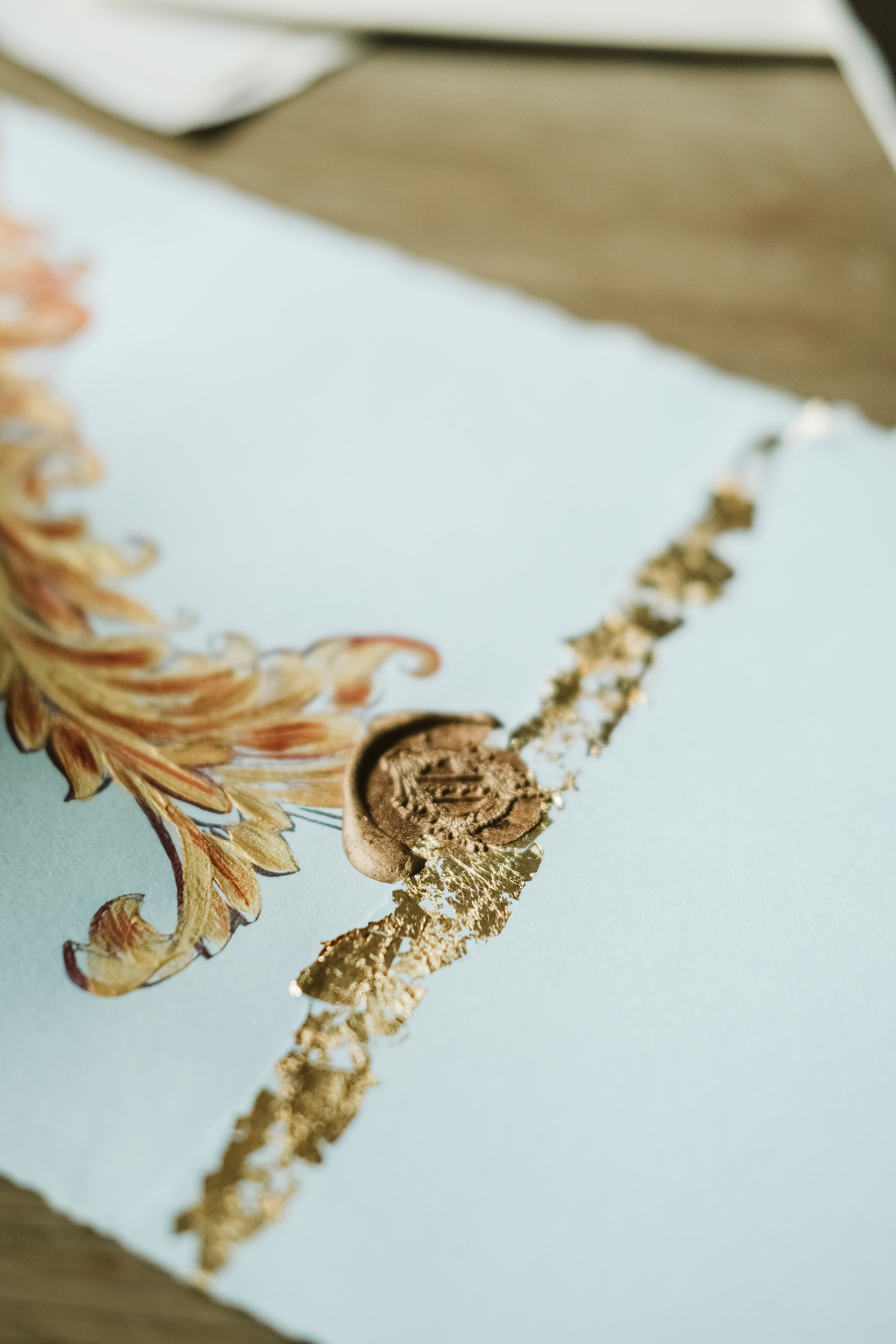 Luxury hand painted wedding invitations showing a blue envelope with gold design