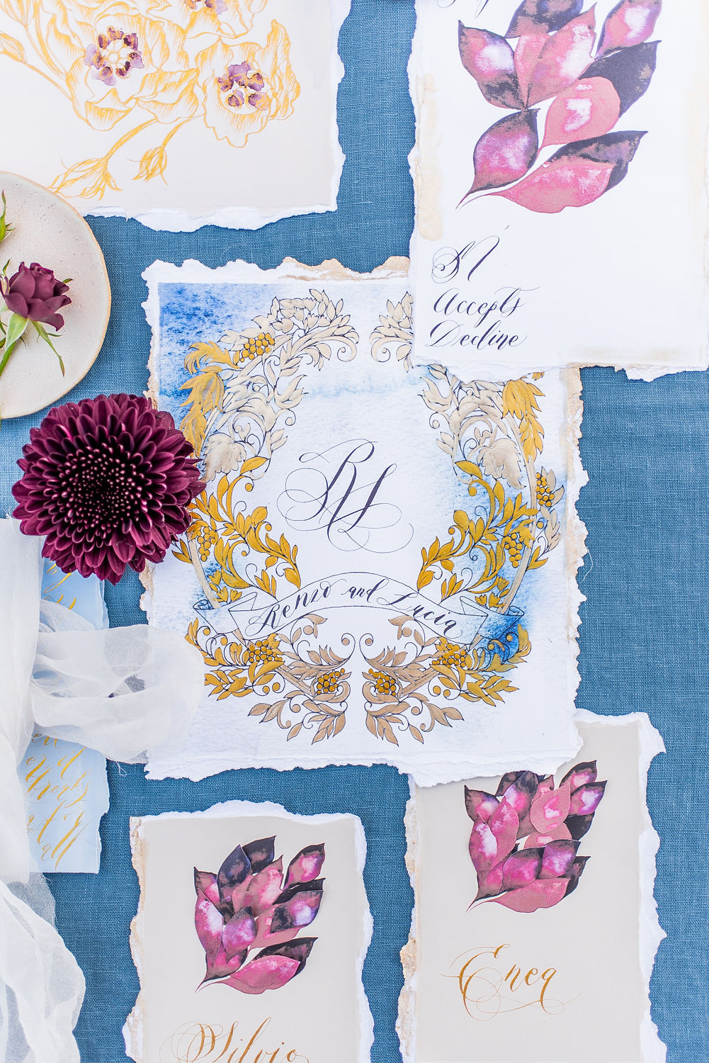 This blogpost is about when you should send out your wedding invitations, showing an invitation suite with blue, gold and red colours.