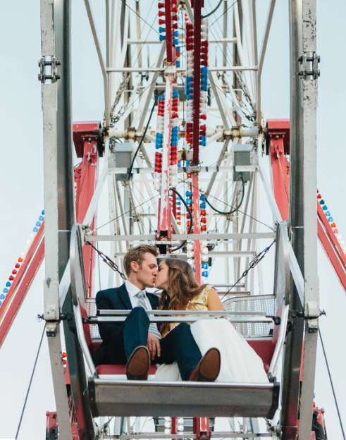 Book a carnival for your wedding, bride and groom riding on a ferris wheel