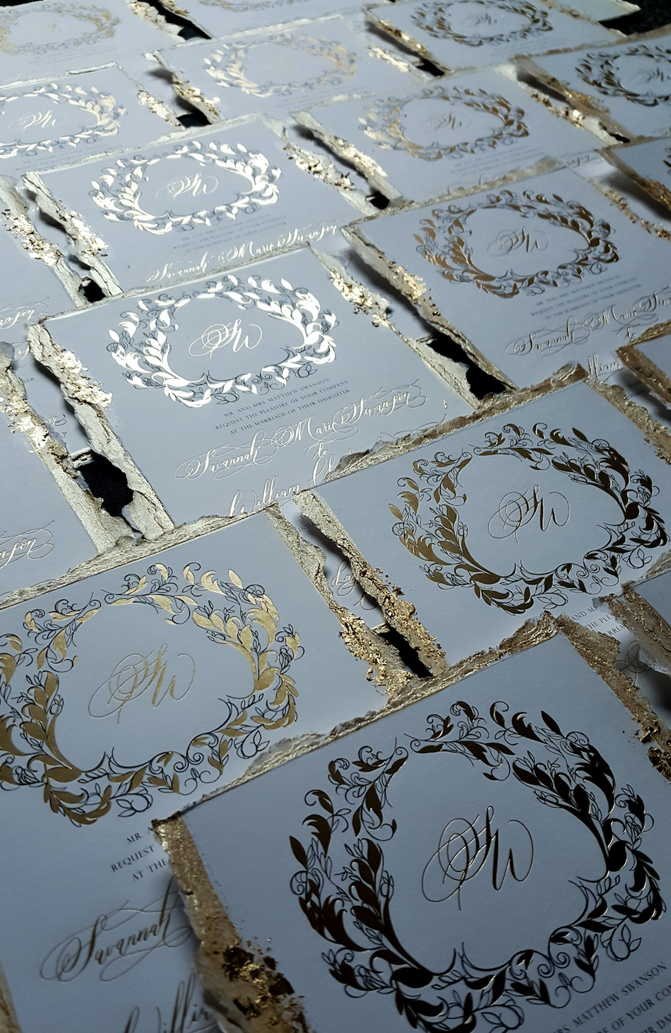 Gold foil wedding invitations with a black and gold crest design