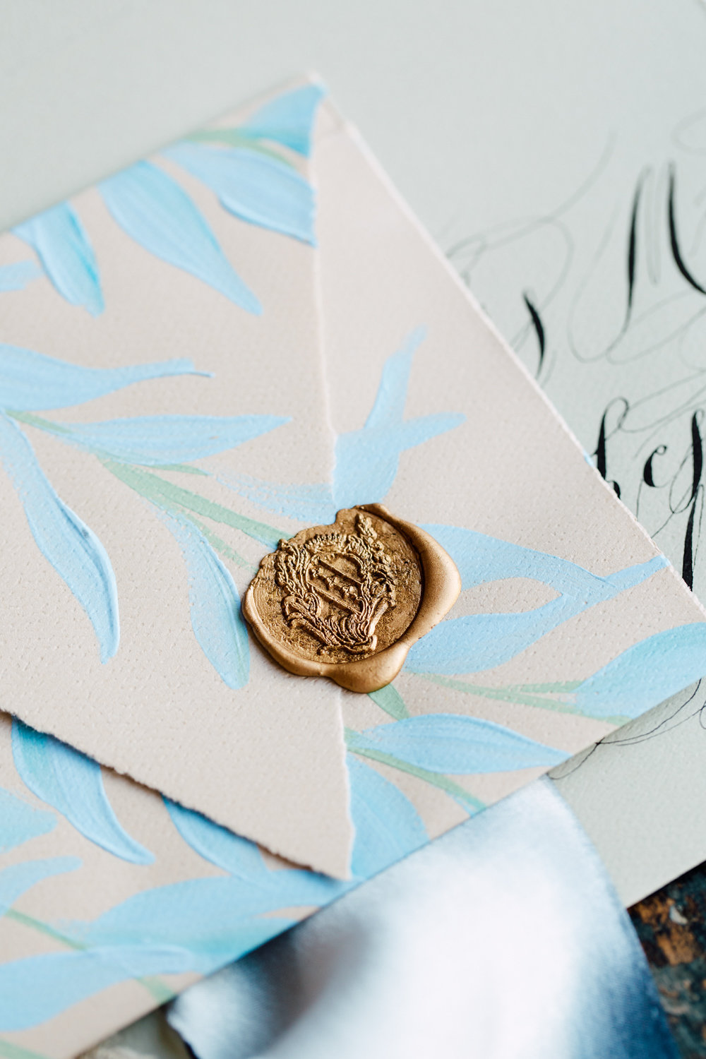 French Inspired Wedding Invitations - blue leaves hand painted envelope detail with a rich gold wax seal
