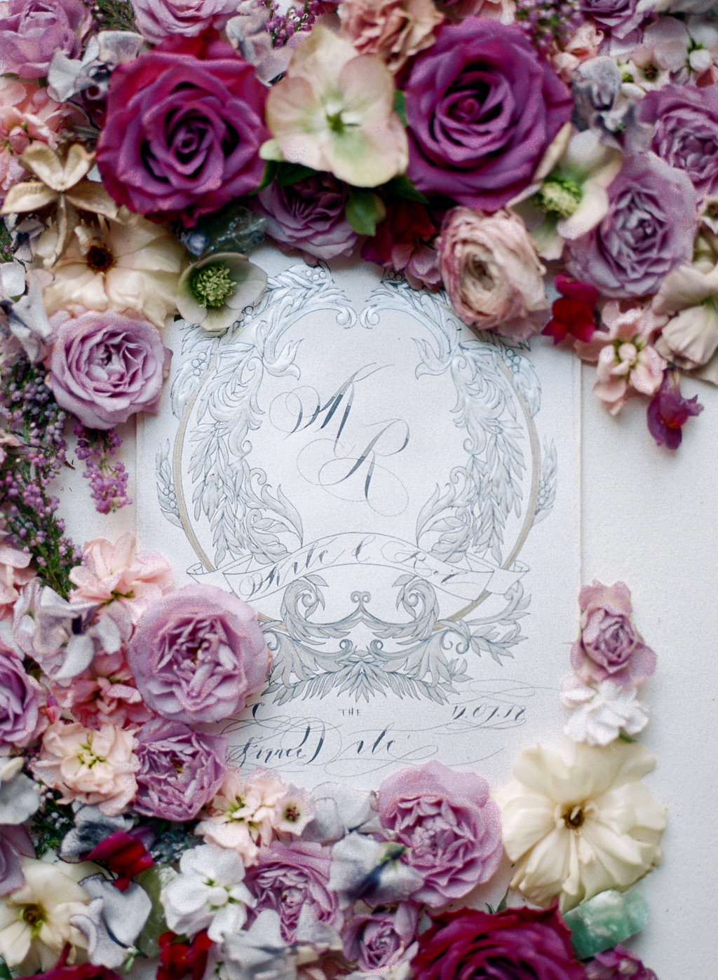 White and silver wedding crest with monogram design and styled with large pink roses