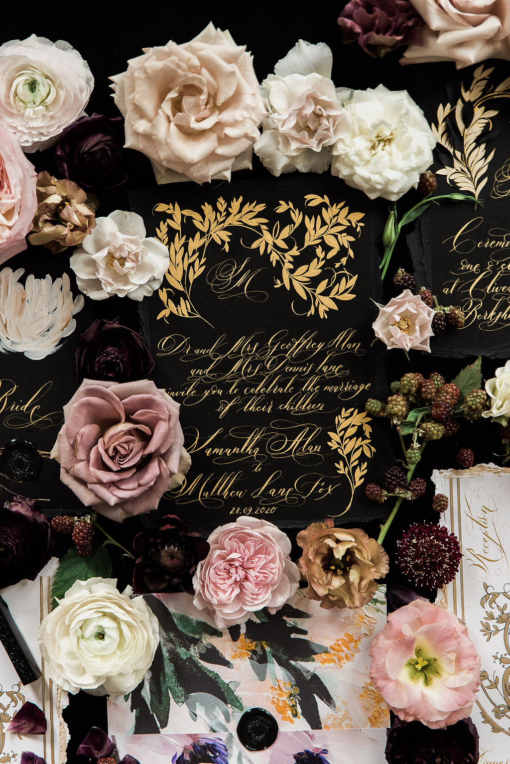 French Style moody black and gold invitations styled with flowers on a black background