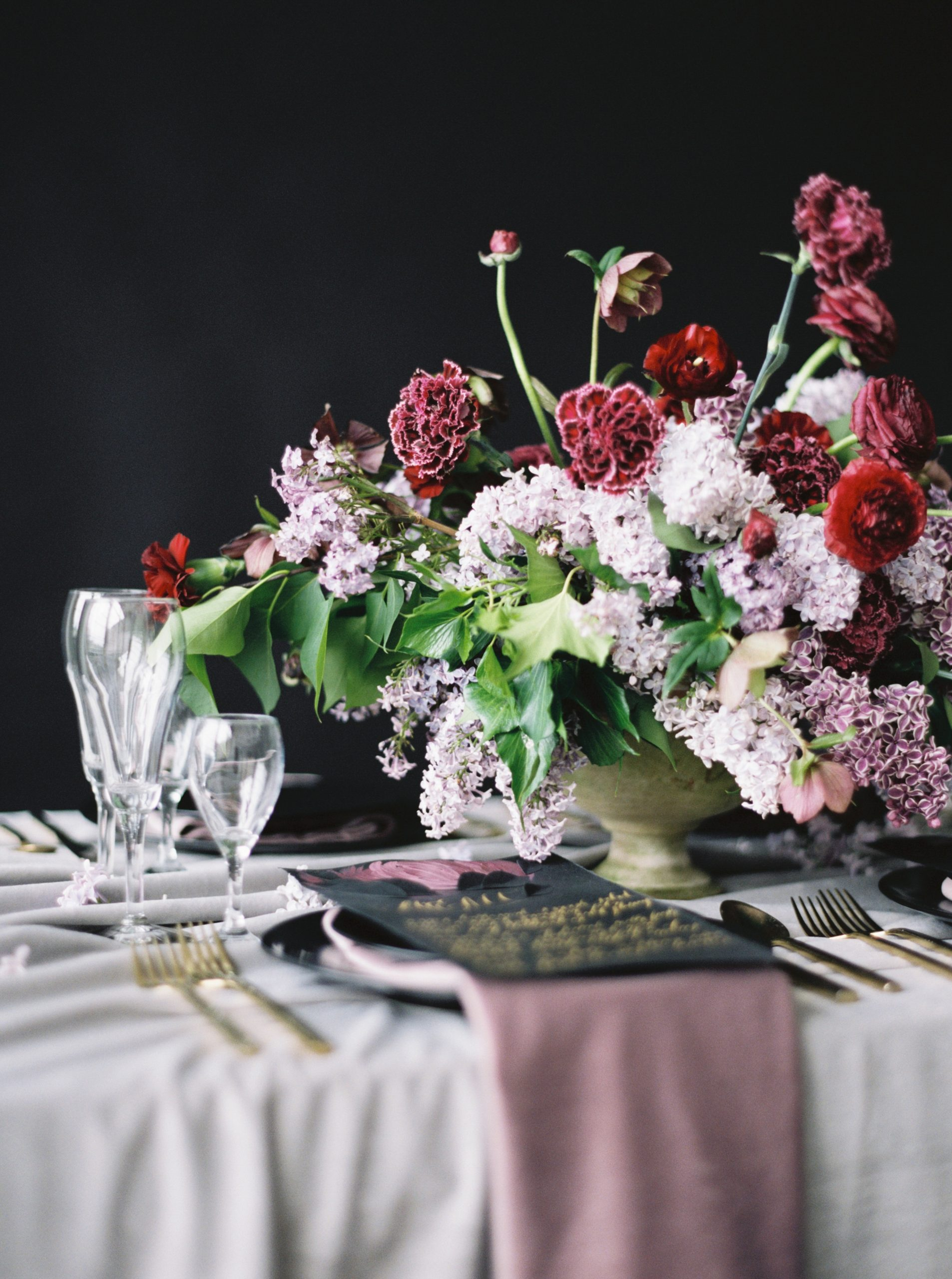 Moody table setting idea with red, lilac flowrs and a black menu design