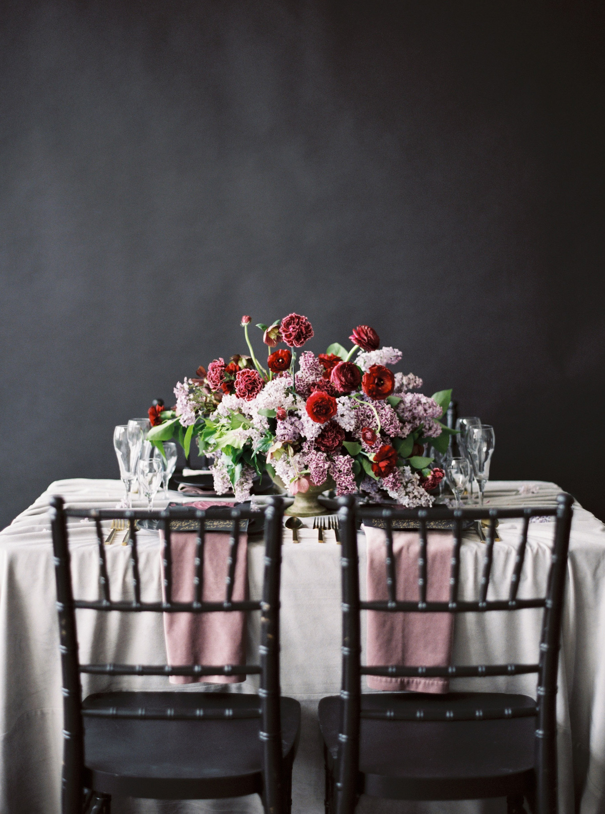 Moody wedding tablescape with black chairs andpale blush table cloth