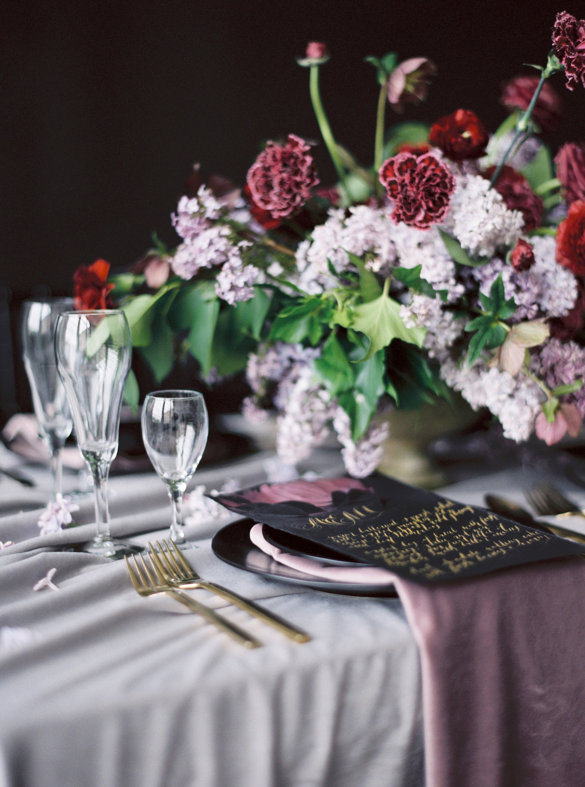 Striking moody table setting idea with black and rich red tones