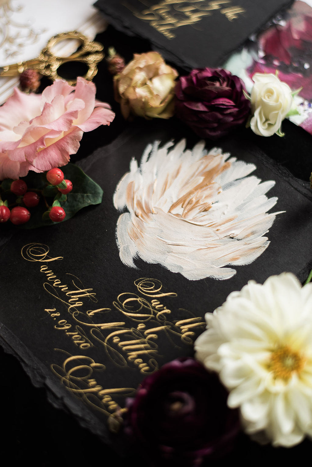 Beautiful fine art wedding inspired black save the date with a hand painted white and gold flower and gold calligraphy