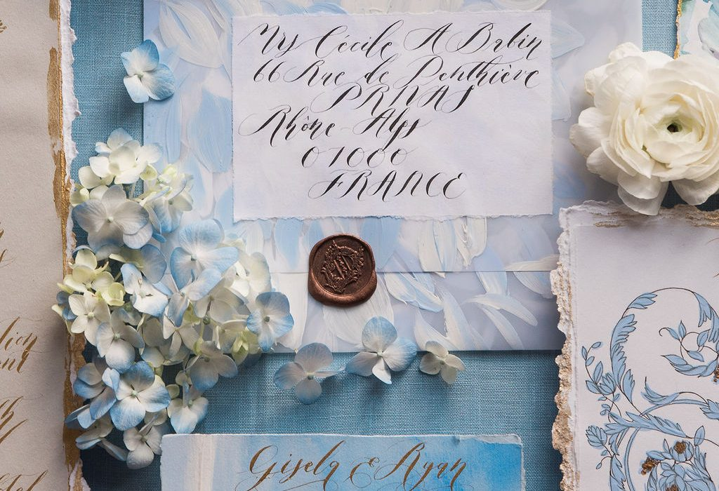 Beautifully styled watercolour wedding invitation suite with vellum envelope and rsvp card with gold calligraphy