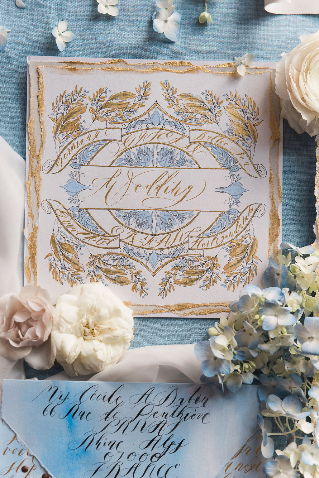 Hand painted wedding invitation card with pale blue and gold hues, paired with fine art gold calligraphy. Perfect addition to a French destination wedding.