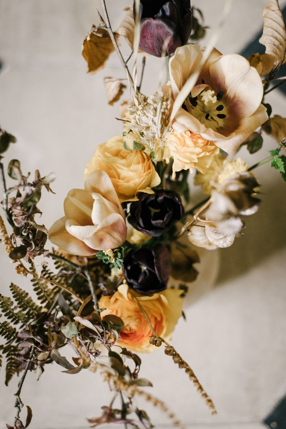 Dark and moody floral wedding inspiration with deep caramel, pale orange and dark purple flowers