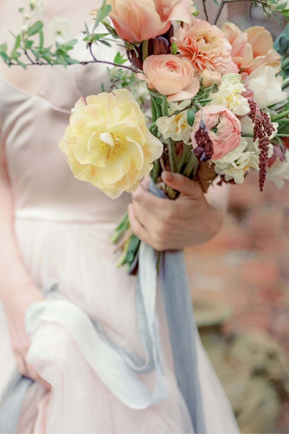 Fine art bridal bouquet with a large yellow rose and smaller blush flowers