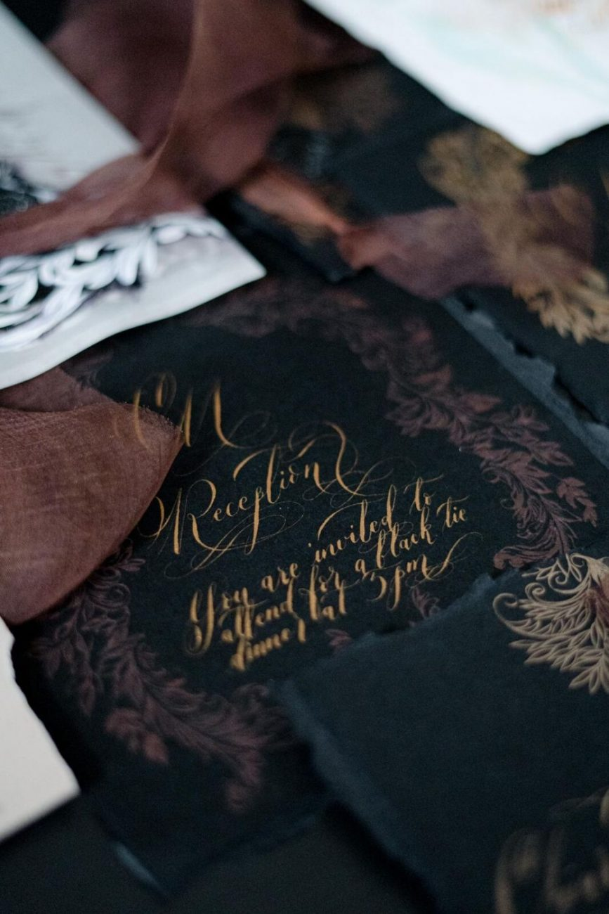 Black and gold wedding reception card with deep brown filigree designs