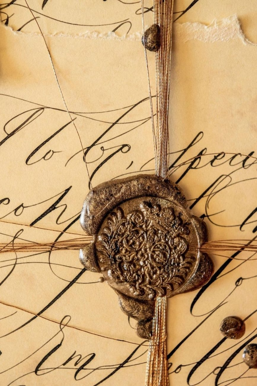 Beautiful fine art editorial calligraphy on deep creme paper with a deep antique gold wax seal for a wedding in Venice