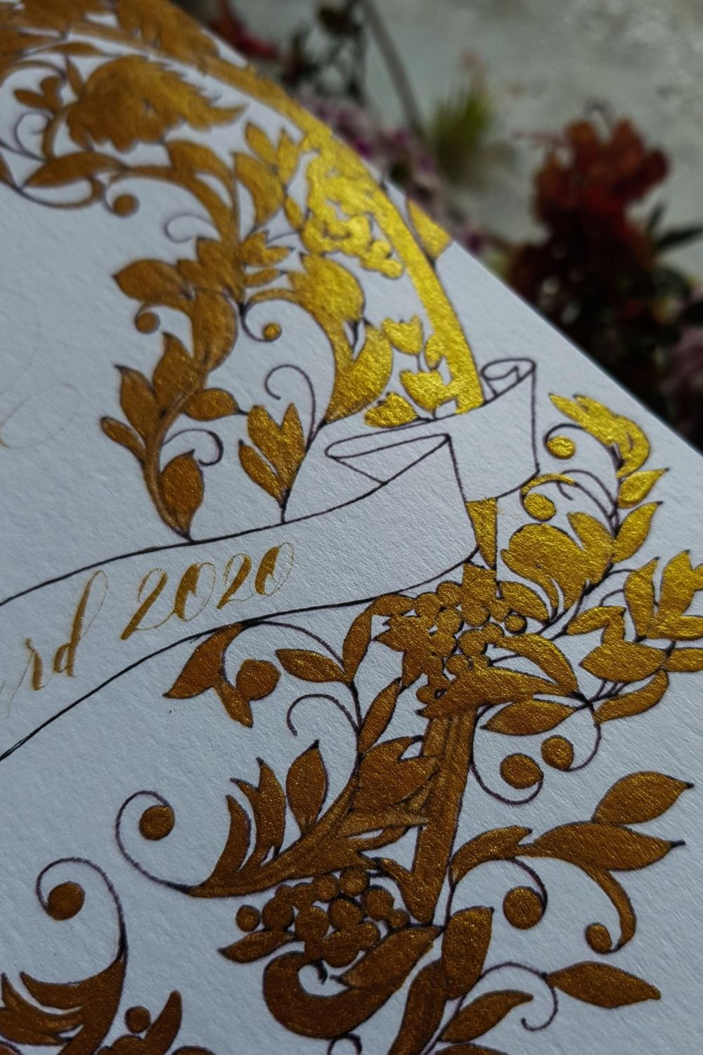 Wedding menu close up detail of a gold crest design with a black outline