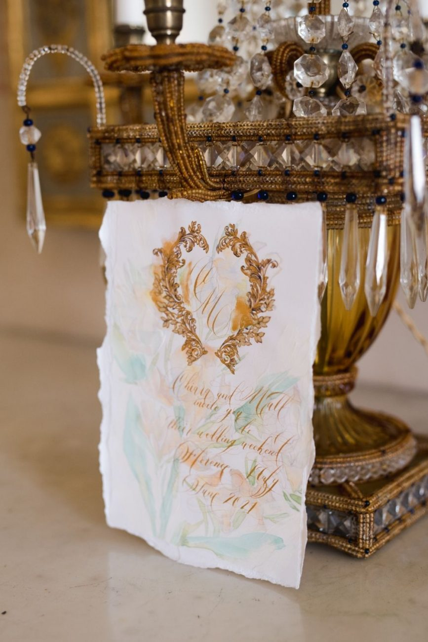 Luxury wedding invitation. Featuring a beautiful, romantic pale green and cream floral watercolour illustration, gold calligraphy, gold hand painted crest design and hand torn edges.