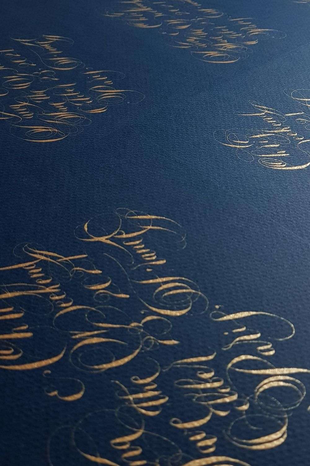 Ornate gold handwritten calligraphy on navy blue for a gold and navy blue invitation design