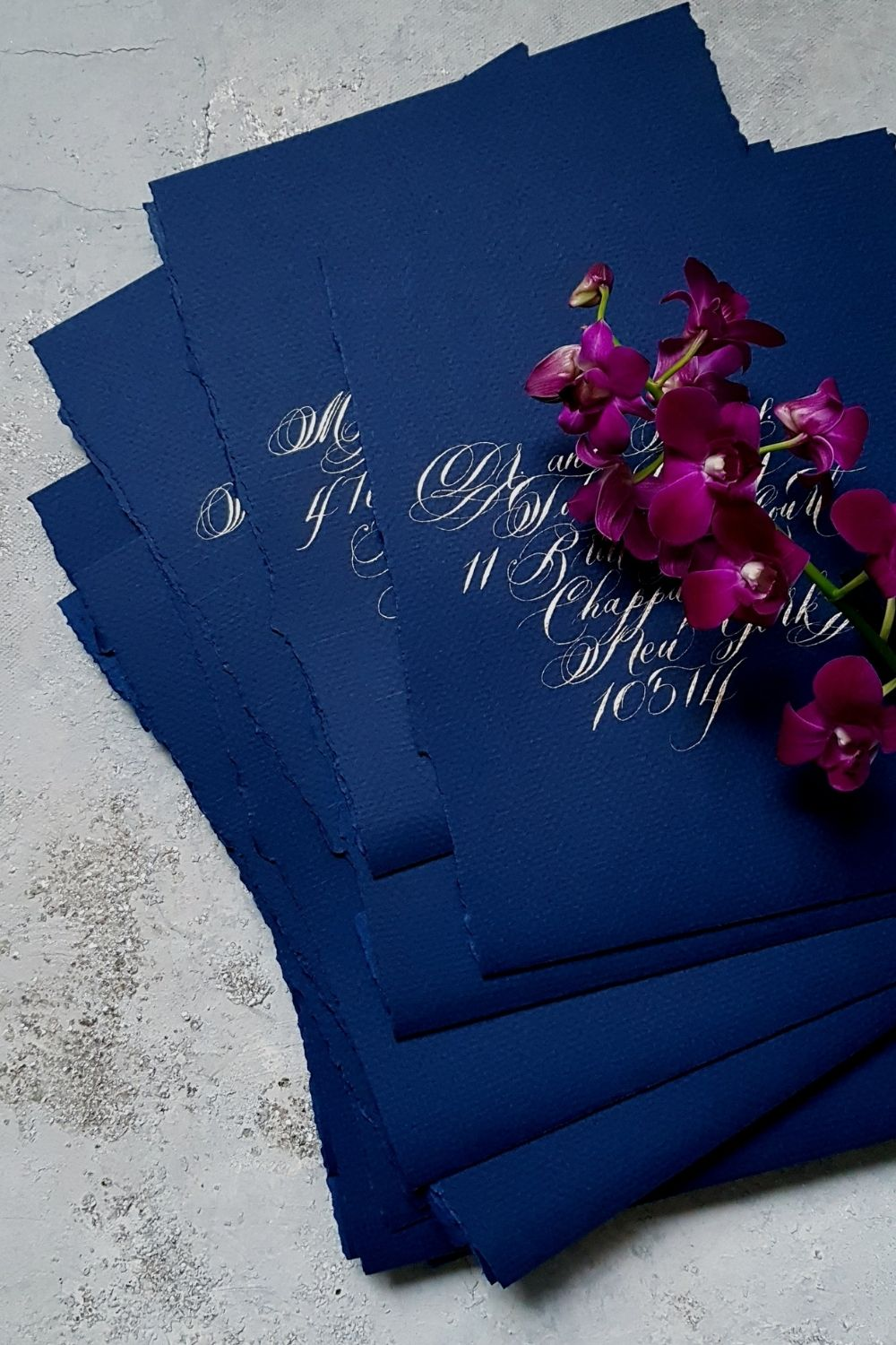 Luxury large hand made envelopes with torn edges and pale gold calligraphy for a navy blue and gold wedding invitations suite