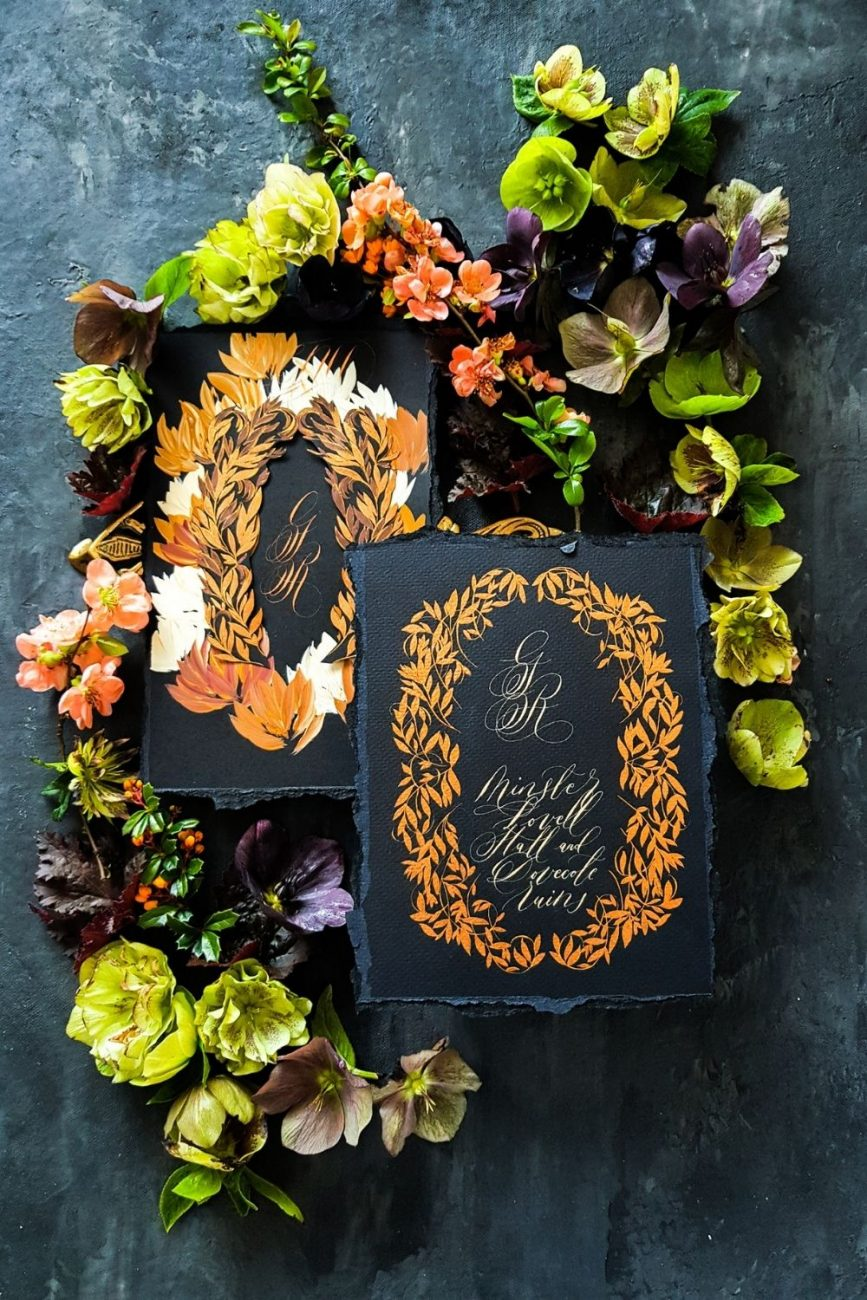 Beautiful, Spanish wedding invitations with dark and moody hues and copper hand painted leaves