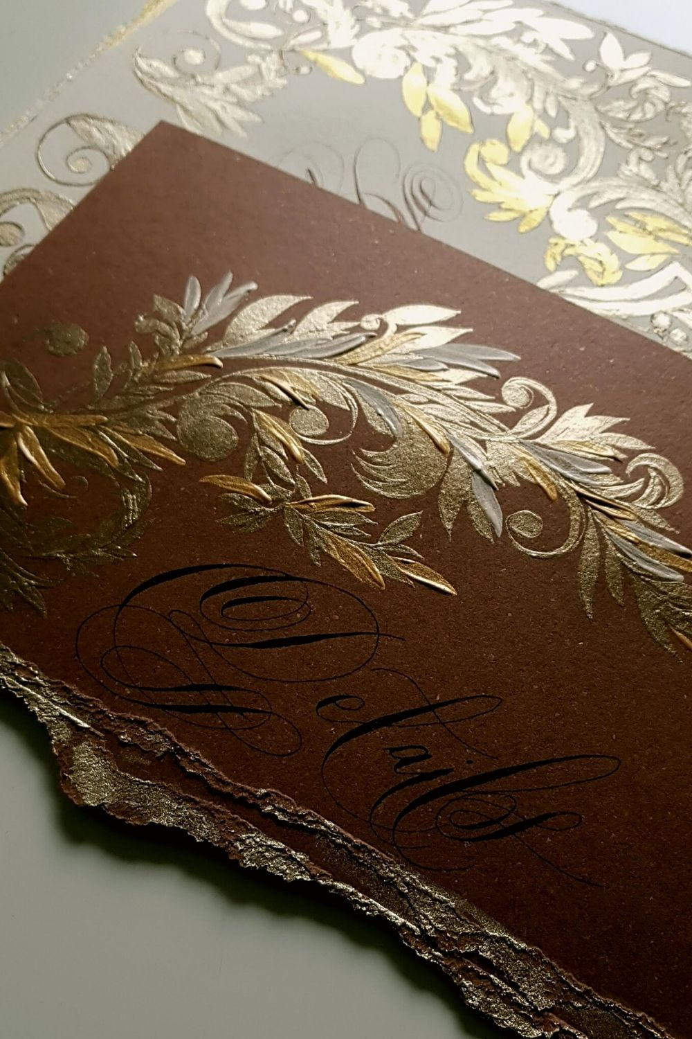 Villa Erba wedding invitations with deep brown card with gold hand painted details and a torn edge