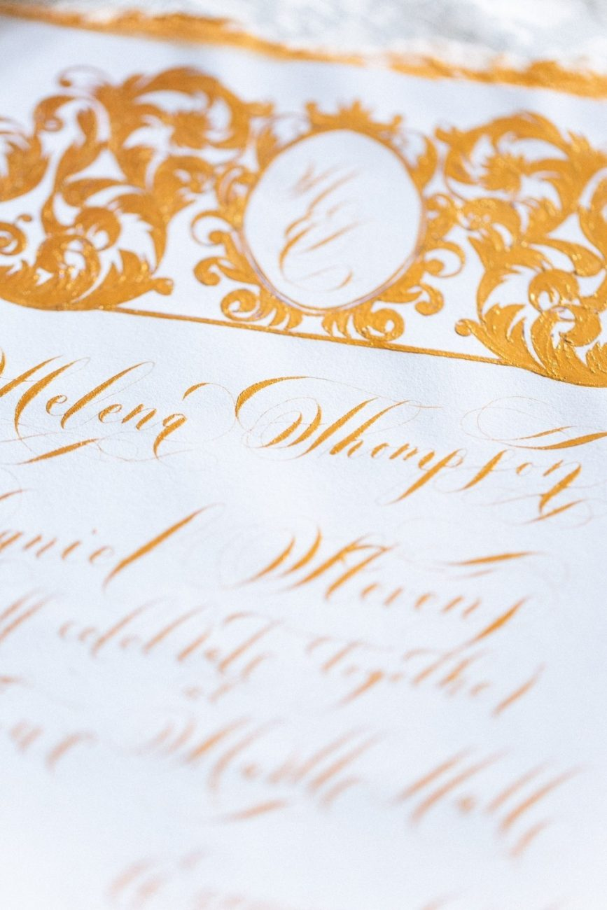 Blue & Gold fine art wedding stationery featuring an invitation card with a large crest design