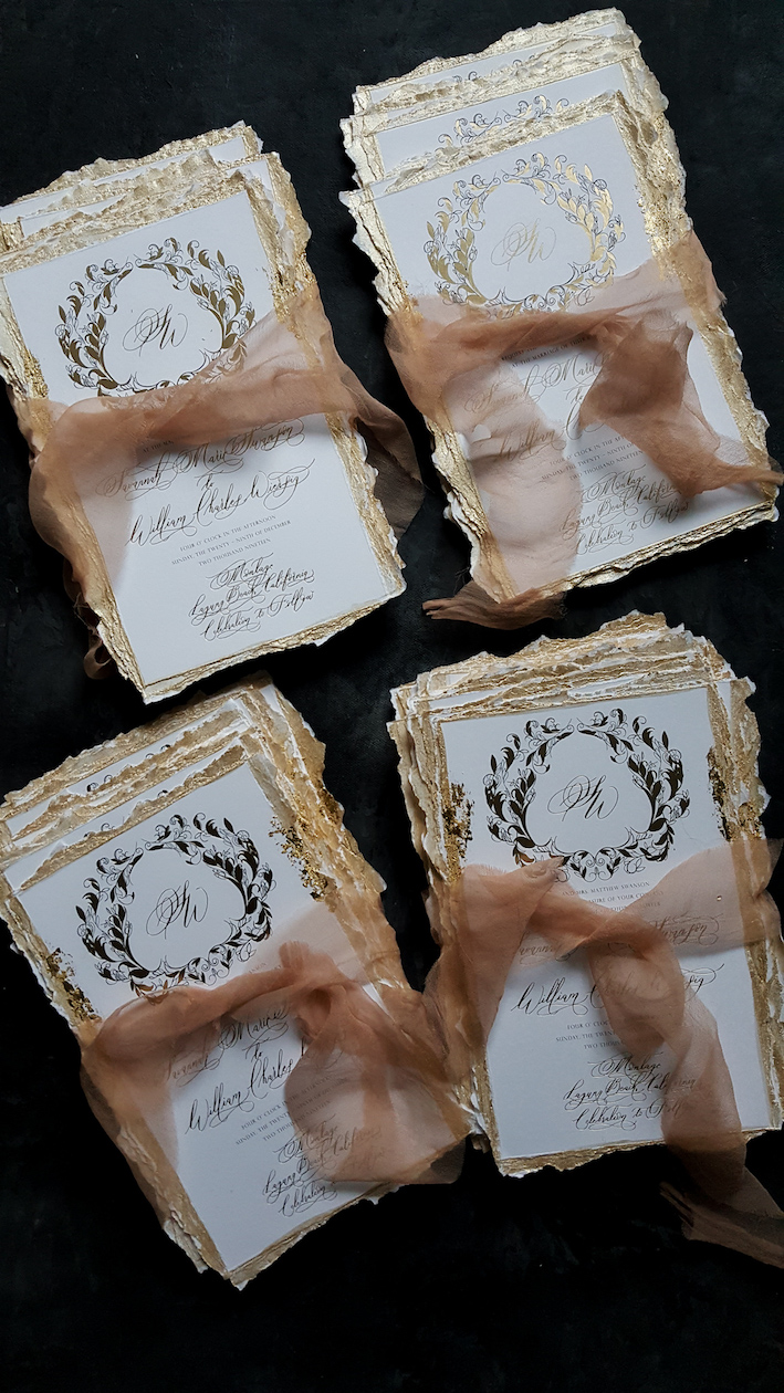 Luxury custom wedding invitations with white and gold foiled invitations with hand torn and hand painted gold edges
