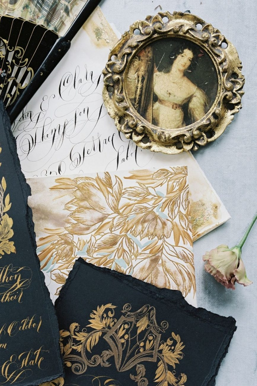 Gold floral invitations detail with flowers and green leaves