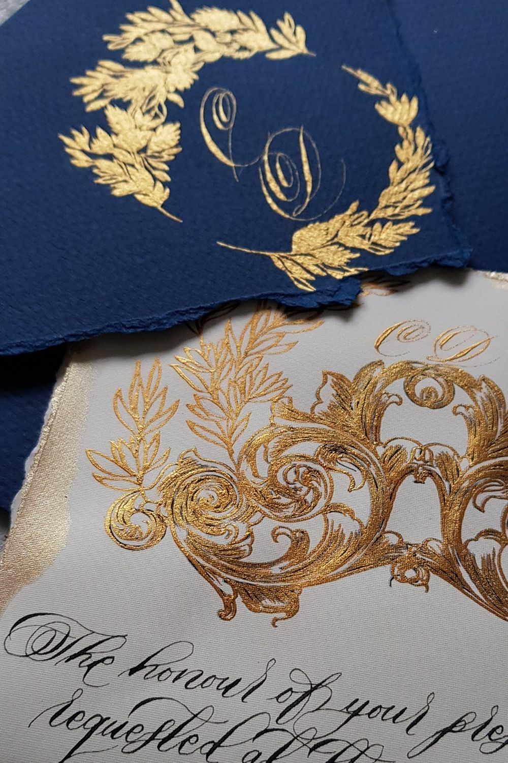 Luxury white and gold wedding invitations with a hand made, gold vintage French style crest design